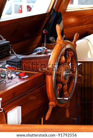 Close up of a steering wheel of the ship made of a wood - stock photo