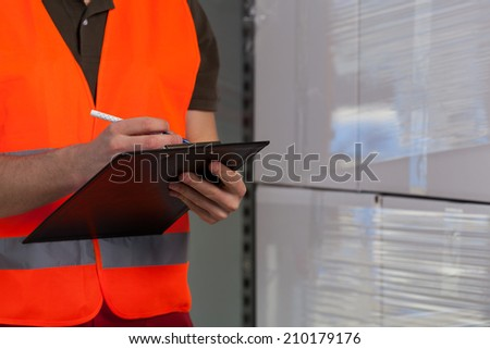 Close-up of a storekeeper signing document on clipboard - stock photo