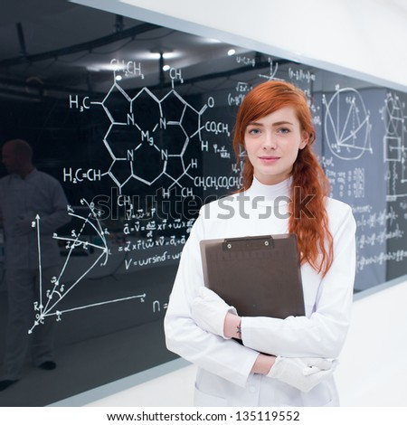 close-up of a student in a chemistry lab smiling and looking in the camera while holding in hands a book and with a blackboard with formulas on the background - stock photo