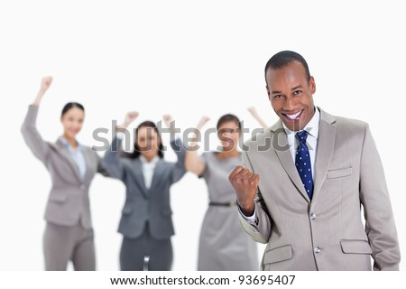 Close-up of a successful business team with man in foreground smiling and clenching his fist with three co-workers raising their arms - stock photo