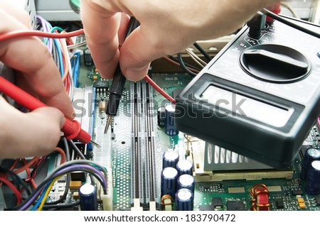 Close-up of a technician hands with voltmeter - stock photo