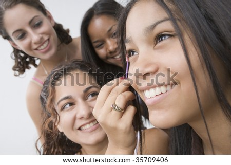 Close-up of a teenage girl applying mascara on her eye with her friends smiling beside her