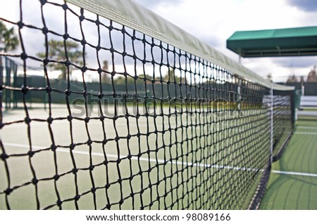 Close up of a tennis net and court on a sunny and cloudy day. - stock photo