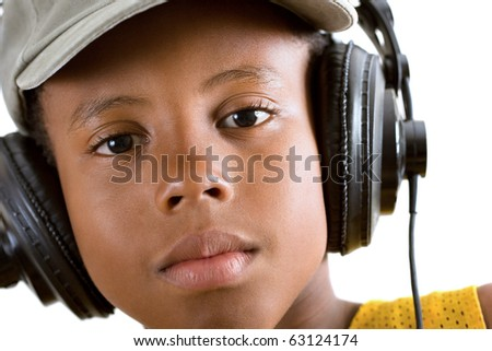 close-up of a tired boy listening to soothing music via headphones - stock photo