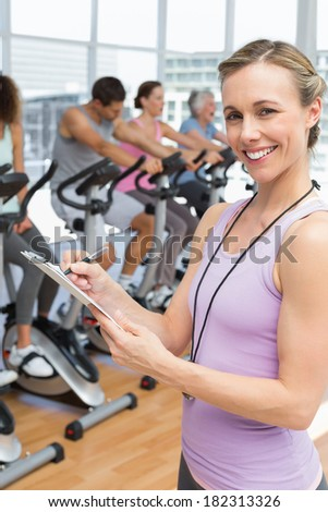 Close-up of a trainer with people working out at spinning class in gym