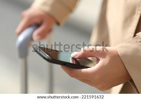 Close up of a traveler woman hand consulting a smartphone and holding a suit case