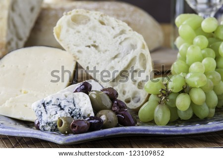 Close up of a tray of assorted rustic bread and cheese with olives and grapes - stock photo