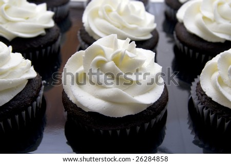 Close up of a tray of chocolate cupcakes with white swirl frosting. - stock photo