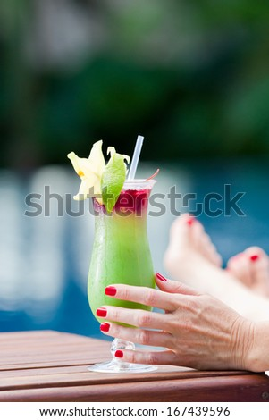 close up of a tropical cocktail served pool side with female hands holding the glass in the rainforest of Belize