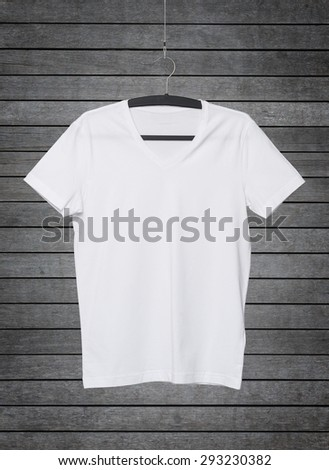 Close up of a V shape white t-shirt on cloth hanger. Dark concrete background. - stock photo