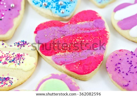 Close up of a variety of colorful heart shaped cookies decorated by children.