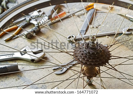 Close up of a very dirty bicycle of rear sprocket wheel and hub with tools - stock photo