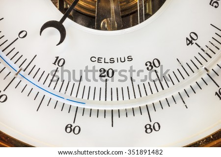 Close up of a vintage circular thermometer with celsius scale