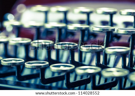 Close up of a vintage maroon color typewriter with black and silver keys - stock photo