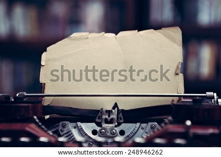 Close up of a vintage typewriter in a library with bookcases from 1920s era - stock photo