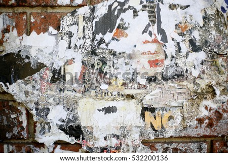 Close up of a wall with many old layers of peeling posters over red brick wall