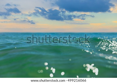 Close up of a wave in the ocean with sun light reflections against a green yellow color sky with clouds