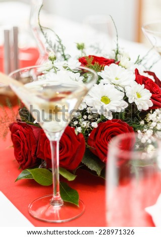 close up of a wedding bouquet on table with red roses and glasses - stock photo