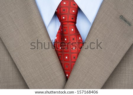 Close up of a well dressed man in a beige suit and jacket with necktie. - stock photo