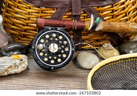 Close up of a wet antique fly fishing reel, rod, landing net, artificial flies and rocks in front of creel with rustic wood underneath. Layout in horizontal format. - stock photo