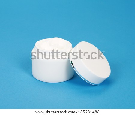 close up of a white beauty cream or yogurt on blue background - stock photo