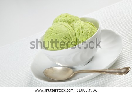 close up of a white bowl with scoops of pistachio ice cream on a white background, macro, detail, horizontal, slanted / Pistachio Ice Cream