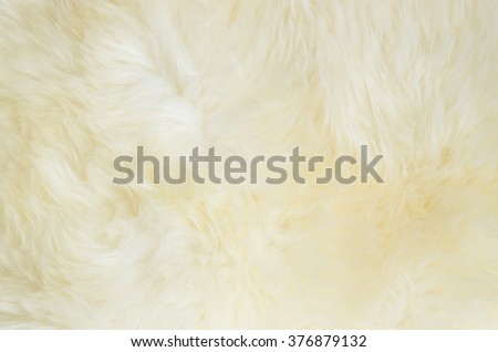 Close up of a white dyed sheepskin rug as a background. - stock photo