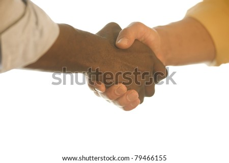 Close-up of a White man and Black man shaking hands. - stock photo