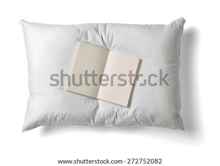 close up of  a white pillow and a book on white background - stock photo