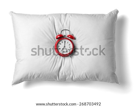 close up of  a white pillow and red alarm clock on white background - stock photo