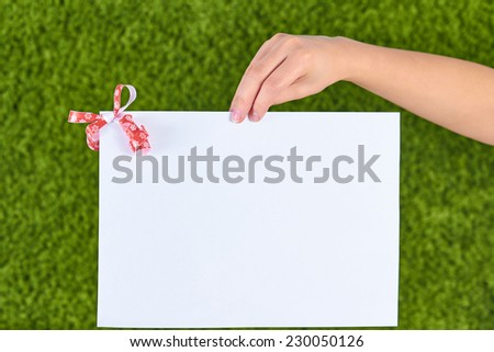 Close-up of a white sheet of paper holding by  woman hand with a red bow,ribbon in a corner isolated on green background. - stock photo