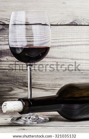 Close-up of a wine glass, a cork and a bottle on a wooden background