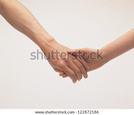 Close-up of a woman and a man holding hand in hand - stock photo