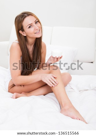 Close-up Of A Woman Applying Lotion On Her Feet - stock photo