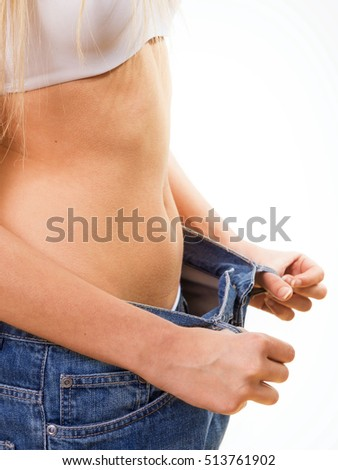 Close-up of a woman belly in a too big pants against white background