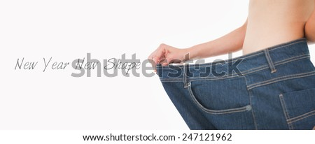 Close up of a woman belly in too big pants against white background - stock photo