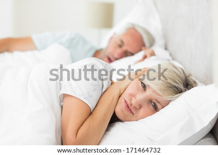 Close-up of a woman covering ears while man snoring in bed at home - stock photo