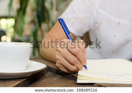 Close-up of a woman drawing into her diary, in the park - stock photo