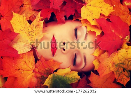 Close-up of a woman face in autumn leafs - stock photo