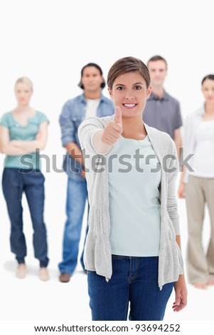 Close-up of a woman giving the thumb-up with people behind against white background - stock photo