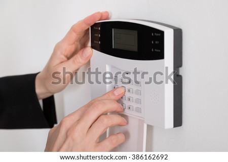 Close-up Of A Woman Hand Entering Code In Security System - stock photo