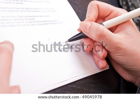 close-up of a woman hand holding pen and signing papers - stock photo