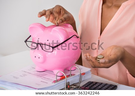 Close-up Of A Woman Hand Inserting Coin In Piggybank - stock photo