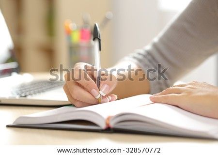 Close up of a woman hand writing in an agenda on a desk at home or office - stock photo