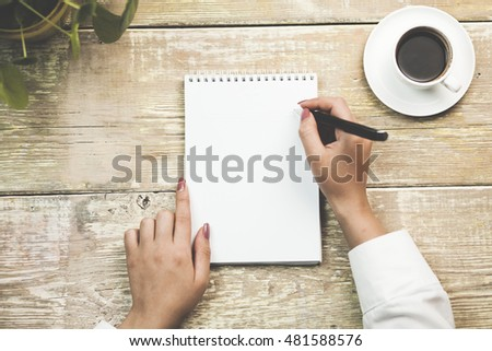 Close up of a woman hand writing in an agenda on a desk at home or office