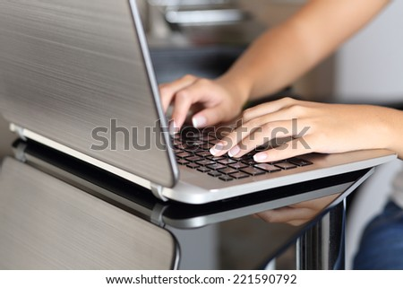 Close up of a woman hands typing in a laptop working at home in the kitchen table - stock photo