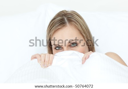 Close-up of a woman hiding in her bed at home - stock photo