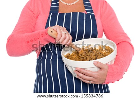 Close up of a woman holding a bowl and mixing the ingredients for a cake, isolated on a white background. - stock photo