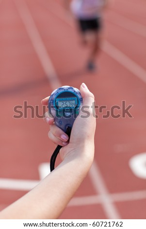 Close-up of a woman holding a chronometer to measure performances of a sprinter in a stadium - stock photo