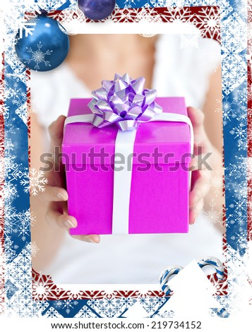 Close up of a woman holding a present sitting on the floor against christmas themed frame - stock photo